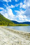 Pristine clean sunny beach with mountains in distance. Summer day at lake. royalty free stock photo