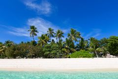 Beautiful fiji island. Pristine empty island at fiji, south pacific, with blue sky, palm trees, white sand beach and turquoise lagoon Royalty Free Stock Photos