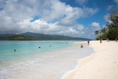 Pristine Getaway at Mystery Island. MYSTERY ISLAND, VANUATU, PACIFIC ISLANDS-DECEMBER 2,2016: Tourists swimming in the Pacific Ocean waters with mountain view Stock Image
