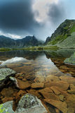 Pristine glacier lake in the Alps and storm clouds Stock Photos