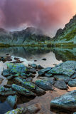 Pristine glacier lake in the Alps and storm clouds at sunset Royalty Free Stock Image