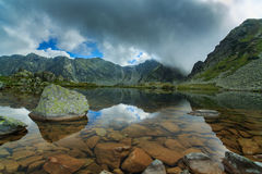 Pristine glacier lake in the Alps and storm clouds at sunset Royalty Free Stock Images