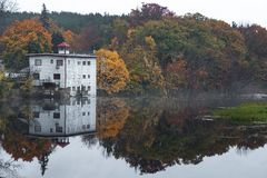 A lake reflects fall foliage on a misty morning. A still lake reflects the fall foliage in New England stock images