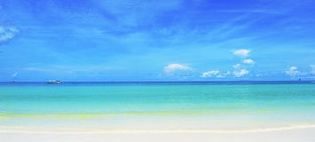 Pristine white sand beach, sea & blue sky meeting in horizon Royalty Free Stock Photography
