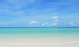 Pristine white sand beach, sea & blue sky meeting in horizon. Pristine white sand beach, tranquil blue sea & clear blue sky with scattered clouds meeting in royalty free stock image