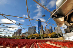 Pritzker Pavilion at Chicago city. Pritzker Pavilion at Millennium Park and city buildngs, Chicago, illinois, USA.  Photo taken in October 6th, 2014 Royalty Free Stock Image