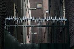 Privé-bezit, omheiningsgebied zwarte metaalpoort met bescherming met weerhaken Oude document geweven achtergrond, retro kleuren stock fotografie
