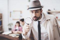 Privé-detectiveagentschap De mens stelt met vergrootglas, houdt de vrouw haar dochter stock afbeeldingen