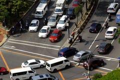 Privé en openbare voertuigen bij een kruising in Pasig-Stad, Filippijnen tijdens het spitsuur in de ochtend Stock Foto's