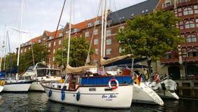 Privé jachten die langs één van de kanalen van Kopenhagen en de kapiteins op hen worden geparkeerd Stock Foto