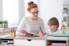 Privé privé-leraar die jonge student helpen stock afbeeldingen