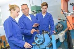 Privé-leraar die stagiairs betreffende machines instrueren stock foto