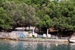 Privé stranden op Middellandse Zee Stoelen, ligstoelen, zonlanterfanters en parasols het wachten op toeristen stock afbeeldingen
