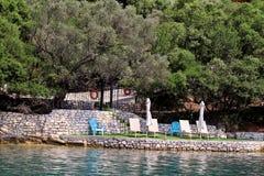 Privé stranden op Middellandse Zee Stoelen, ligstoelen, zonlanterfanters en parasols het wachten op toeristen royalty-vrije stock fotografie