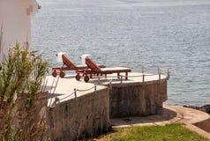 Privé stranden op Middellandse Zee Stoelen, ligstoelen, zonlanterfanters en parasols het wachten op toeristen royalty-vrije stock afbeelding