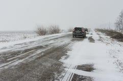 Privé vervoer op een sneeuwwegstrijd vooruit door snow-drift Stock Afbeeldingen