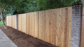 Privacy cedar fence with brick accents showing horizontal. In a suburb a privacy cedar fence with brick accents lined with bark dust on a quiet street Royalty Free Stock Photo