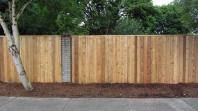 Privacy cedar fence with brick accents showing horizontal. In a suburb a privacy cedar fence with brick accents lined with bark dust on a quiet street Royalty Free Stock Image