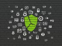 Privacy concept: Broken Shield on wall background. Privacy concept: Painted green Broken Shield icon on Black Brick wall background with  Hand Drawn Security Royalty Free Stock Image