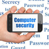 Privacy concept: Computer Security on Hand Holding. Privacy concept: Hand Holding Smartphone with  blue text Computer Security on display on wall  Tag Cloud Royalty Free Stock Image
