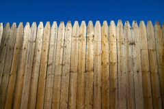 Privacy Fence. Tall wooden fencing around a home or construction site to keep people out. Blue sky background Stock Photography