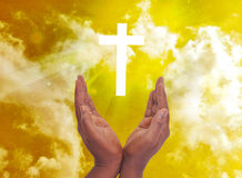 PRIVACY WITH SPIRITUAL CHRISTIAN CROSS. Male hands in spiritual intimacy before the Christian cross with rays of light, wilt answer prayers royalty free stock photo