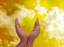 PRIVACY WITH SPIRITUAL. Male hands in spiritual intimacy in a yellow frame of sky with rays of light to wilt answer prayers Stock Photography