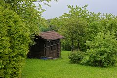 Garden shed in spring by lush green trees and lawn Stock Image
