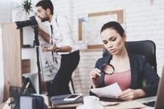 Privat detektiv- byrå Mannen ser in camera, kvinnan ser fotothrouthförstoringsglaset royaltyfria foton