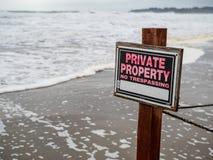 Privat egenskap inget inkräkta tecken på pol- och trådstaketet på strandegenskap bredvid vågor royaltyfria bilder