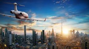 Privat jetflyg ovanför den Dubai staden arkivbild