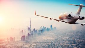 Privat jetflyg ovanför den Dubai staden i härlig solnedgångli arkivbild