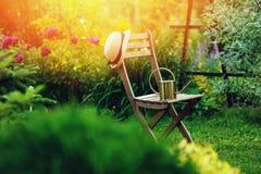 privat trädgård för härlig blommande sommar med trästol fotografering för bildbyråer