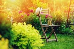privat trädgård för härlig blommande sommar med trästol royaltyfria bilder