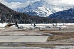 Privata strålar och en helikopter på flygplatsen av St Moritz Arkivbild