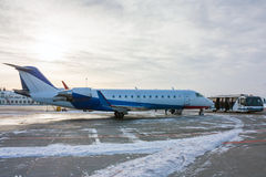 Private aircraft and apron bus. In a cold winter airport Royalty Free Stock Photo