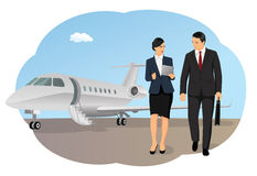 Private aircraft arrival. Businessman and businesswoman by airplane on runway. Private aircraft arrival. Working with portable devices Royalty Free Stock Photo