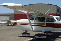 Private airplane - Cessna 172. A Cessna 172 Skyhawk airplane is tied down at the airport.  Colorful hangar is in the background Royalty Free Stock Images