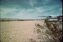 Private airplane landing on ground in the middle of nowhere stock video