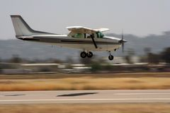 Private airplane landing - panning. Private airplane approaching runway for a landing. Panning shot Stock Photo