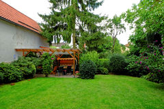 Private backyard garden idyll in summer. Garden idyll in summer by lush green colors. The backyard with loggia and garden furniture of a German home Royalty Free Stock Photos