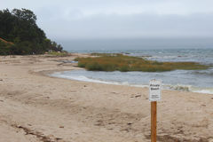 Private beach. White private beach sign with beach during a storm in background Stock Image