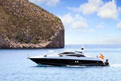 Private beautiful yacht sailing fast close to Alicante coast in Spain. Motor yacht sailing in the coast of Calpe in Alicante in a sunnt day in east coast of Stock Photography