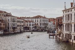 Private boat on Grand Canal in Venice, UK. Private boat on Grand Canal in Venice with colourful houses on both sides. Boats are the main mode of transport in Royalty Free Stock Photo