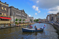 Private Boat Ride on Amsterdam Canal with Flag of the Netherlands Royalty Free Stock Photography
