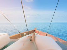 Private boat trip on open sea. Image shows legs of a woman lying on a thick and comfortable cushion laid on top of boat. Royalty Free Stock Photography