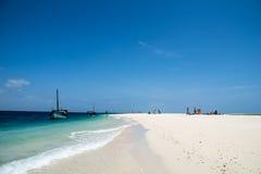 Private Boote und weißer sandiger Strand mit europäischen Touristen, eine kleine Ferninsel im Indischen Ozean, Tansania Stockfotografie