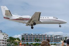 Private business jet aircraft preparing to land. Private business jet aircraft with wheels down preparing to land on tropical Caribbean island. People watching royalty free stock images