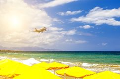 Private business plane on landing flies over sandy beach with sun loungers on background of sunset, sun and clouds. Private business plane on landing flies over royalty free stock images
