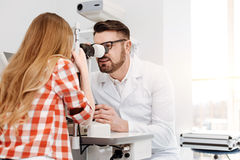 Private careful doctor employing professional opthalmometer. Lets see what we have. Successful talented well known ophthalmologist using special machinery for Royalty Free Stock Photography